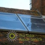 Torn old plastic solar water heating flat panel repaired with polycarbonate sheet